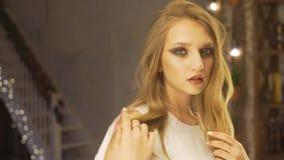 Retrato de la bastante, joven y sensual mujer con maquillaje hermoso y el peinado elegante que miran su reflexión adentro metrajes
