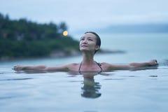 Retrato de la belleza asiática que sonríe y que se relaja en piscina en el amanecer foto de archivo libre de regalías