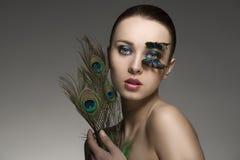 Retrato de la belleza con las plumas del pavo real Imágenes de archivo libres de regalías
