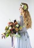 Retrato de la belleza de primavera de una novia con una guirnalda y un ramo adentro Fotos de archivo