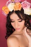 Retrato de la belleza de una mujer con una guirnalda de flores en su cabeza un fondo rojo Imagen de archivo