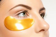 Retrato de la belleza de una muchacha atractiva con un remiendo del oro debajo del ojo fotografía de archivo libre de regalías