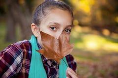 Retrato de la boca de ocultación de la muchacha con la hoja del otoño Foto de archivo