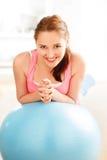 Retrato de la bola relajante atractiva de la aptitud de la mujer joven en el gimnasio Imágenes de archivo libres de regalías