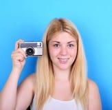 Retrato de la cámara femenina joven del vintage que se sostiene contra el CCB azul Imagen de archivo libre de regalías