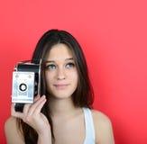 Retrato de la cámara femenina joven del vintage que se sostiene contra la parte posterior del rojo Imagenes de archivo