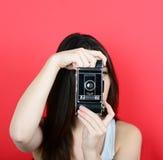 Retrato de la cámara femenina joven del vintage que se sostiene contra la parte posterior del rojo Imagen de archivo