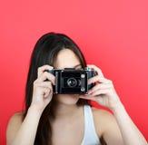 Retrato de la cámara femenina joven del vintage que se sostiene contra la parte posterior del rojo Fotos de archivo libres de regalías