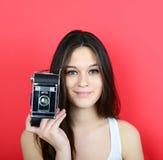 Retrato de la cámara femenina joven del vintage que se sostiene contra la parte posterior del rojo Foto de archivo