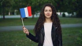 Retrato de la cámara lenta de la bandera que agita del patriota francés de la mujer de Francia con sonrisa alegre y la mirada de  metrajes