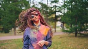 Retrato de la cámara lenta del estudiante de mujer joven lindo que se divierte en el festival de Holi que lanza su pelo pintado c metrajes