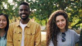 Retrato de la cámara lenta del grupo multi-étnico alegre de las muchachas y de los individuos que se coloca en el parque, sonrien almacen de video