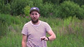 Retrato de la cámara lenta del hombre divertido barbudo joven con la AUTORIZACIÓN de la demostración del casquillo BUENA y el lau almacen de metraje de vídeo