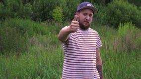 Retrato de la cámara lenta del hombre divertido barbudo joven con gesto de mano ACEPTABLE del casquillo almacen de video