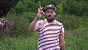 Retrato de la cámara lenta del hombre divertido barbudo joven con la mano ACEPTABLE de la demostración del casquillo metrajes
