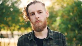 Retrato de la cámara lenta del hombre joven barbudo serio en la camisa militar del estilo que se coloca en el parque en día y la  almacen de video