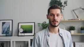 Retrato de la cámara lenta del hombre joven hermoso que mira la cámara que se coloca en casa metrajes