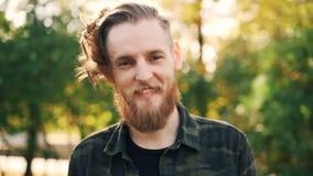 Retrato de la cámara lenta del individuo despreocupado con el pelo, la barba justa y el bigote colocándose al aire libre sonrient almacen de video