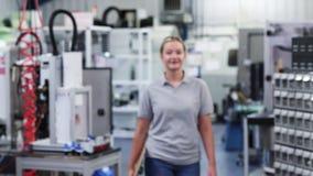 Retrato de la cámara lenta del ingeniero de sexo femenino en fábrica que camina hacia cámara almacen de metraje de vídeo