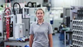 Retrato de la cámara lenta del ingeniero de sexo femenino en fábrica que camina hacia cámara almacen de video