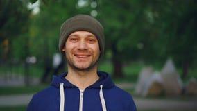 Retrato de la cámara lenta del primer del deportista feliz que sonríe y que mira la cámara que se coloca en parque en primavera a metrajes