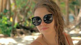 Retrato de la cámara lenta del primer de la mujer joven europea hermosa en gafas de sol, pelo que sopla en viento en la playa tro almacen de metraje de vídeo