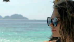 Retrato de la cámara lenta del primer de la mujer joven europea hermosa en gafas de sol, pelo que sopla en viento en la playa tro metrajes