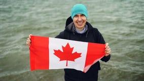 Retrato de la cámara lenta del viajero alegre del hombre joven que sostiene la bandera canadiense en manos y que mira la cámara c metrajes
