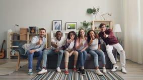 Retrato de la cámara lenta de la gente joven que corre al sofá que se sienta mostrando los pulgares-para arriba almacen de video