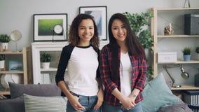 Retrato de la cámara lenta de las señoras jovenes hermosas asiáticas y de la situación afroamericana en casa, mirando la cámara y metrajes