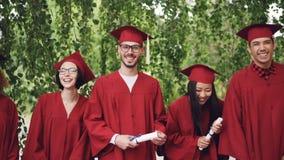 Retrato de la cámara lenta de los estudiantes de graduación que se colocan en la línea que sostiene los diplomas y que ríe mirand metrajes