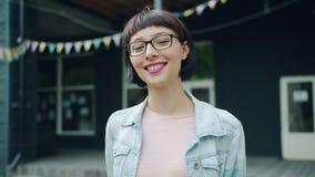 Retrato de la cámara lenta de la morenita joven que mira la cámara y que sonríe al aire libre almacen de metraje de vídeo
