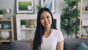 Retrato de la cámara lenta de la muchacha asiática atractiva en la situación blanca de la camiseta en casa moderna, sonriendo y m almacen de metraje de vídeo