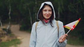 Retrato de la cámara lenta de la muchacha bonita del viajero alegre del mundo en la capa encapuchada que agita la bandera español almacen de video