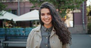 Retrato de la cámara lenta de la muchacha hermosa con la situación larga del pelo rizado al aire libre almacen de video