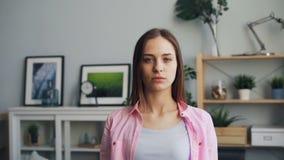 Retrato de la cámara lenta de la mujer joven seria que mira la cámara que se coloca en casa almacen de metraje de vídeo