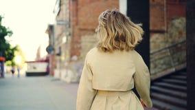 Retrato de la cámara lenta de la mujer joven sonriente en capa de moda que camina en la calle, dando vuelta a la cámara y mirando almacen de video