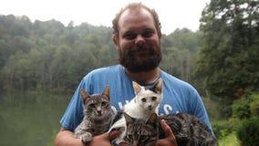 Retrato de la cámara lenta de un hombre barbudo adulto que sostiene tres gatitos bajo la lluvia almacen de metraje de vídeo