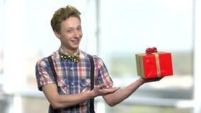Retrato de la caja de regalo de ofrecimiento del muchacho almacen de video