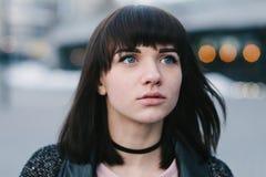 Retrato de la calle de la muchacha morena hermosa joven con los ojos azules grandes y mirada interesada Fotografía de archivo