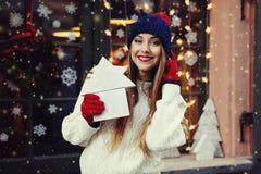 Retrato de la calle de la mujer joven hermosa sonriente que sostiene la casa de madera del juguete Señora que lleva el invierno c Foto de archivo libre de regalías