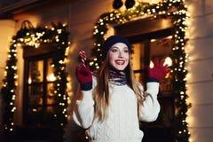 Retrato de la calle de la noche de la mujer hermosa joven que actúa ropa hecha punto elegante emocionada, que lleva Alegría de ex Foto de archivo