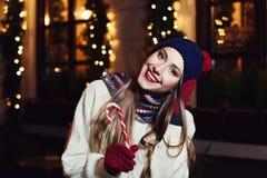 Retrato de la calle de la noche de la mujer joven hermosa sonriente con el bastón de caramelo de la Navidad Looking modelo en la  Fotos de archivo libres de regalías