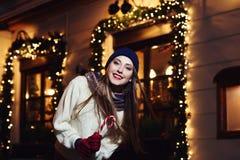 Retrato de la calle de la noche de la mujer joven hermosa sonriente con el bastón de caramelo de la Navidad Looking modelo en la  Imagenes de archivo