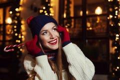 Retrato de la calle de la noche de la mujer joven hermosa sonriente que habla en el teléfono móvil y que mira para arriba Obra cl Fotos de archivo