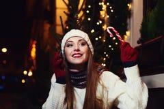Retrato de la calle de la noche de la mujer joven hermosa sonriente que se sienta en café y que habla en el teléfono móvil Mirada Fotos de archivo libres de regalías