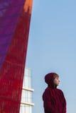 Retrato de la calle del adolescente que lleva la sudadera con capucha rojo oscuro en el fondo de cristal del edificio alto Imágenes de archivo libres de regalías