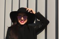 Retrato de la calle de la mujer joven sonriente en la ha brimmed ancha de moda fotografía de archivo libre de regalías