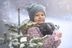 Retrato de la calle de la niña en el sombrero del gato con un muñeco de nieve que goza de la primera nieve fotos de archivo libres de regalías