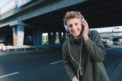 Retrato de la calle de un estudiante feliz en auriculares en el jefe de un fondo de la ciudad Un hombre joven divertido camina al Imagen de archivo libre de regalías